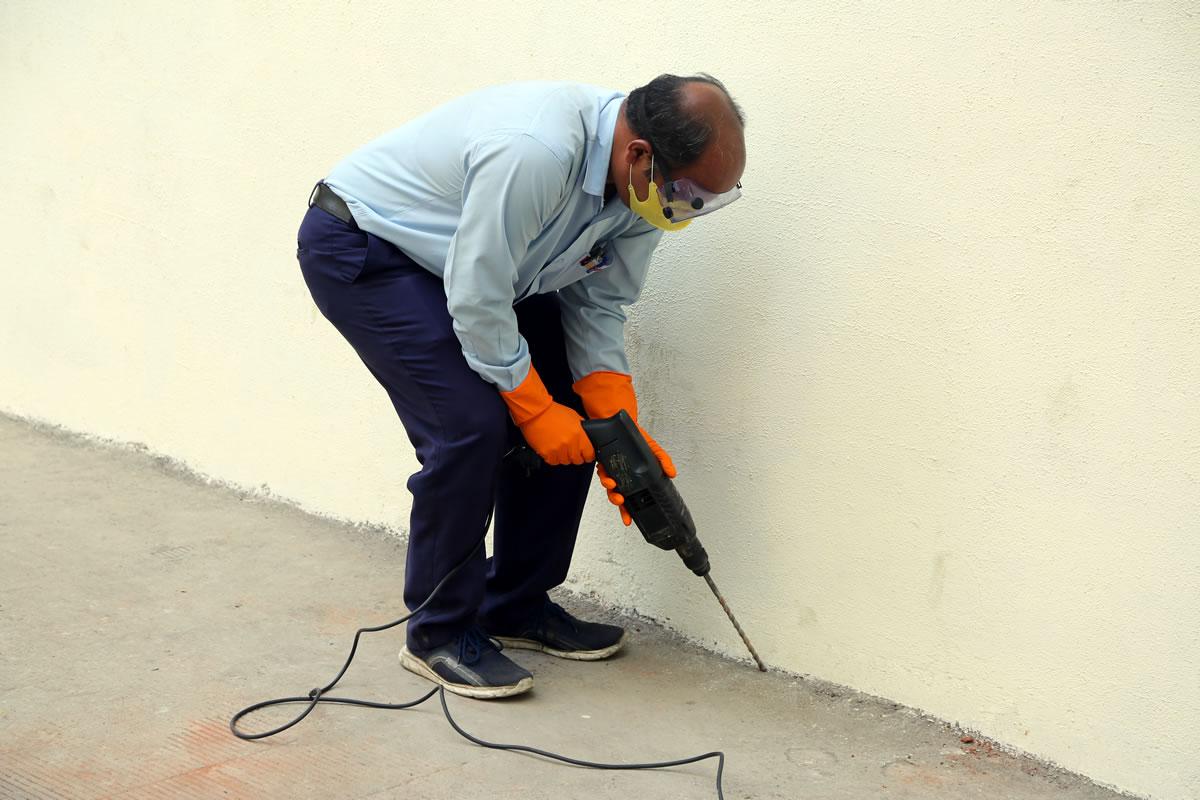 Building exterior drilling for termite treatment